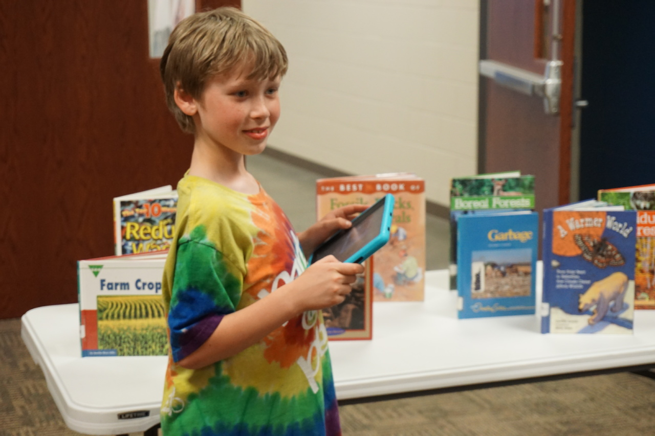Elementary student with iPad in front of books