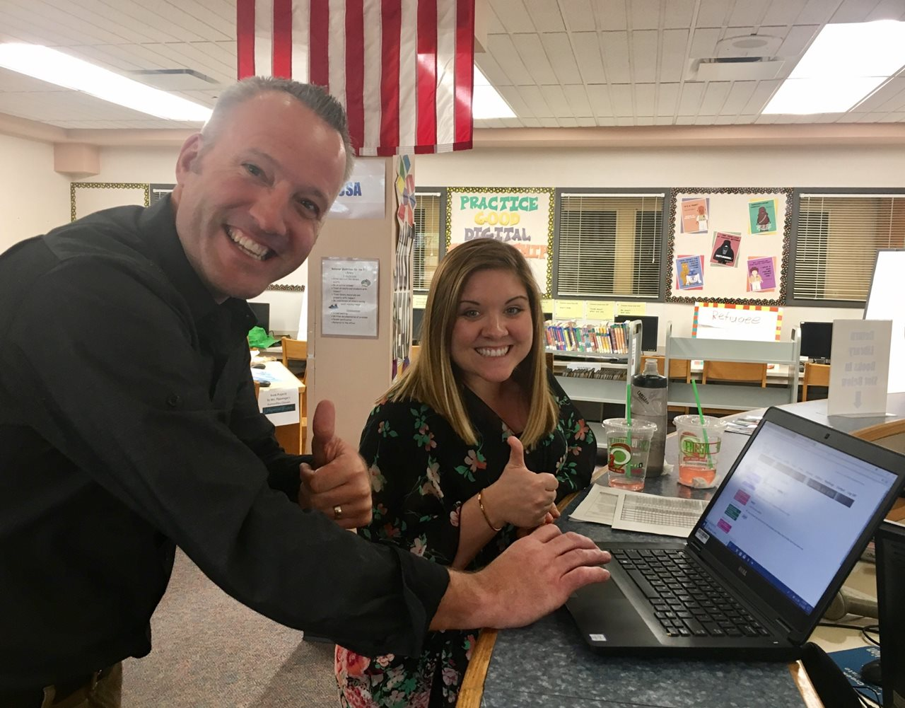 Two adults giving a thumbs up in front of a laptop