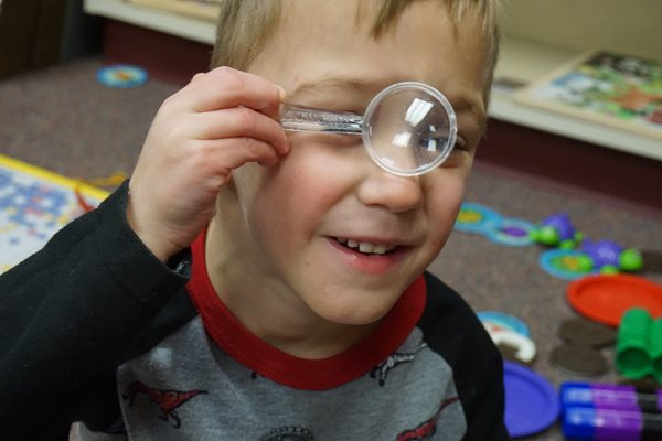 student with magnifying glass